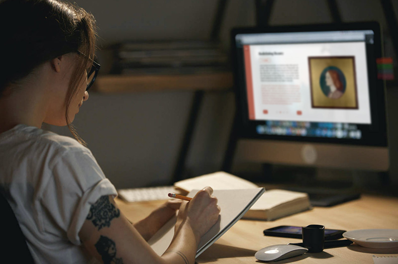 Image of a young person sat at a desk with the OACE intervention on their laptop.