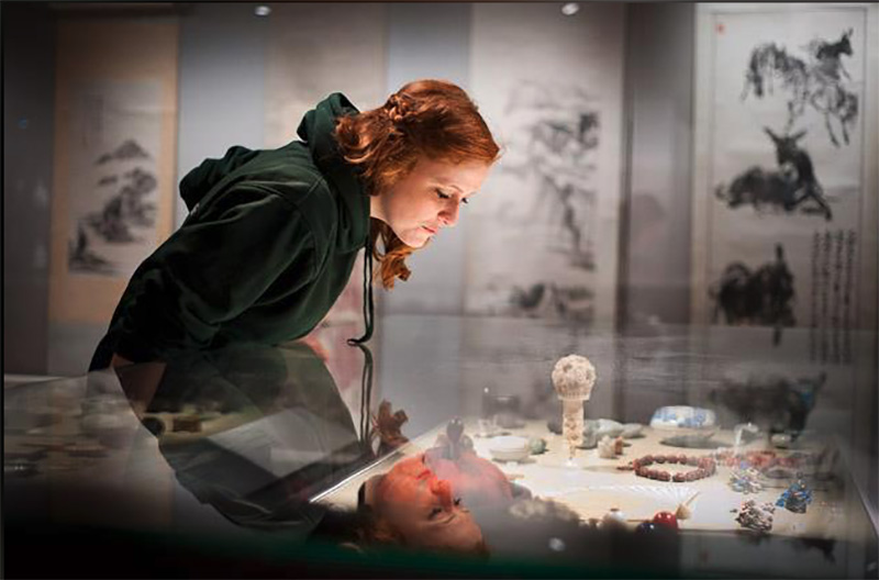 Young woman peering into a desktop display of ceramics in the Ashmolean Museum.