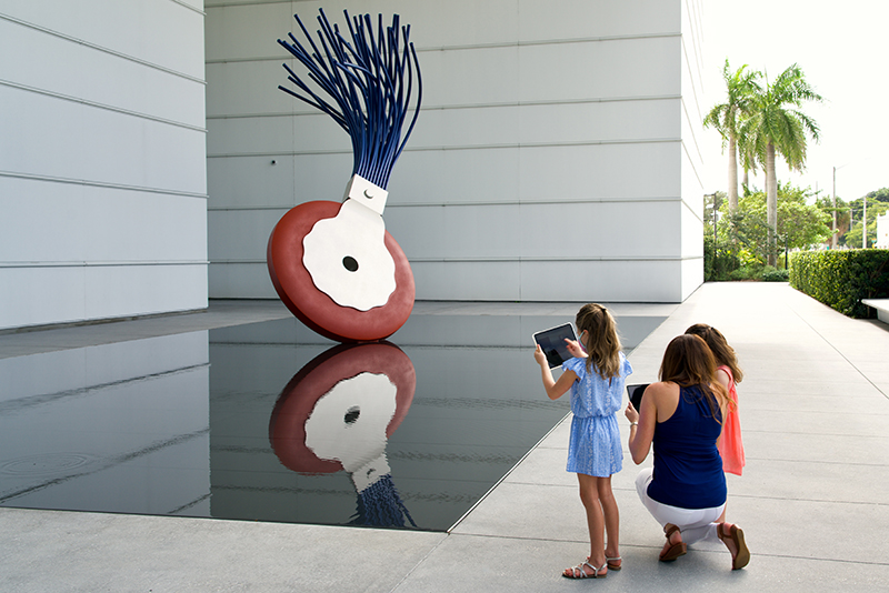 A family standing with iPads in front of a sculpture of a typewriter eraser.