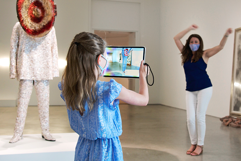 A young person holding an iPad in an art gallery.
