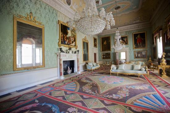 A ornately decorated interior with colorful carpet and large glass chandelier lit by daylight