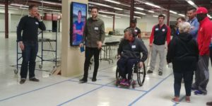 Alt image text: Centre Screen team members present prototype software. A mockup running track is marked out with tape on the floor and a portrait wall-mounted monitor displays Carmelita Jeter. A Paralympic athlete using a wheelchair is at the start of the track and standing athletes stand around him watching.