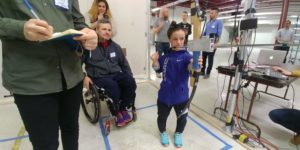 Two Paralympian athletes participate in the user testing of an archery game bow. One of the athletes is holding the bow and looking ahead at a target. One onlooker is making notes in a notebook and another takes a photograph.
