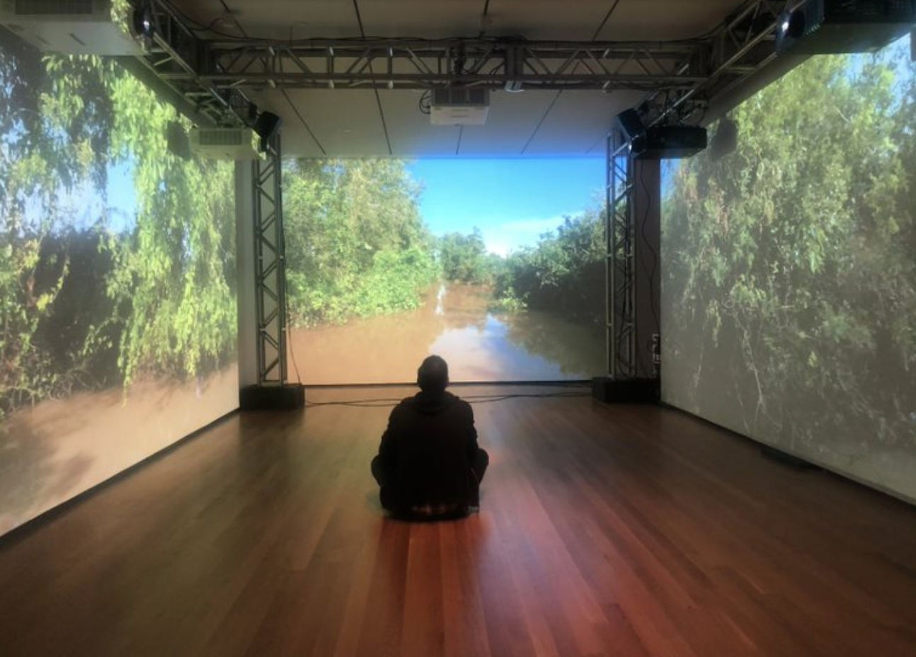person sitting in room with projected walls