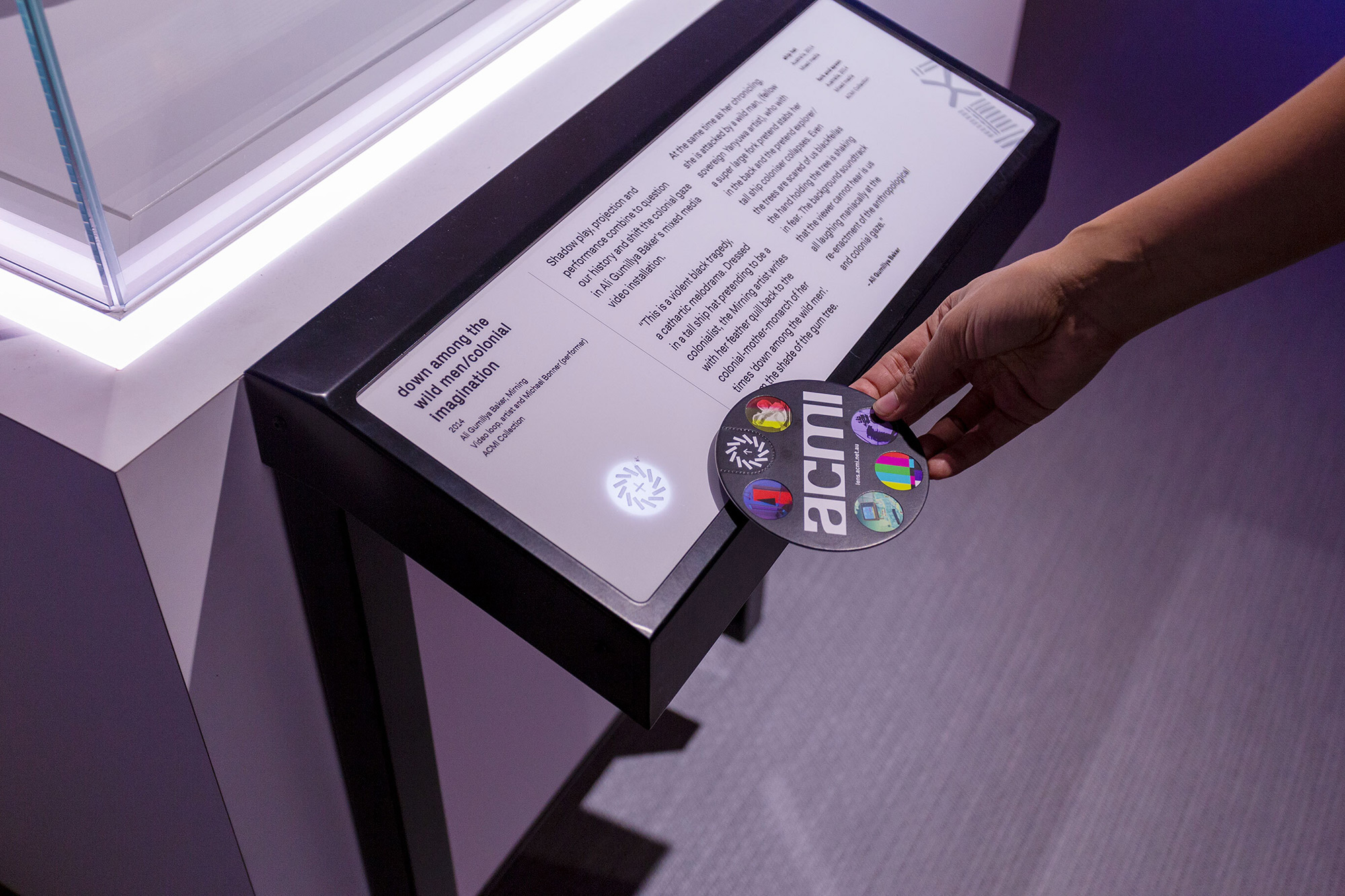 The ACMI Lens tapping on a Lens Reader embedded in a museum label