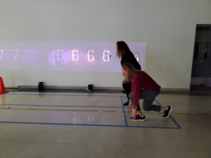 A mockup running track is marked out with tape on the floor and gameplay content is projected on an adjacent wall. Two athletes participating in user testing crouch ready to sprint down the track.