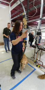 A Paralympian athlete with a guide dog participates in the user testing of an archery game bow. The athlete is holding and interacting with the bow.