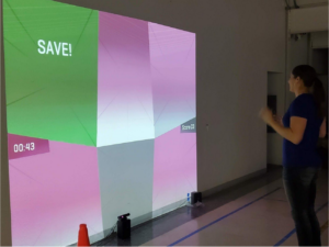 An athlete participates in the user testing of projected gameplay software. The projection displays colored areas with a numerical timer and gameplay score. The word 'save' is also displayed on the project. On the floor in front of her are two audio speakers and a motion-detecting camera.