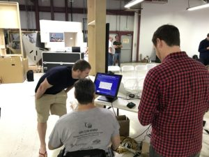 A Centre Screen team member presents an interactive software prototype to a Paralympian athlete using a wheelchair and an Olympian athlete who interacts with the screen.